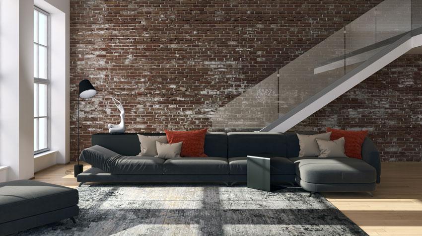 parete in stile vintage in mattoni rossi con divano nero.