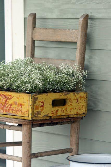 Fioriera dallo stile vintage con vecchia cassetta in legno coca cola poggiata su una sedia sotto al portico.