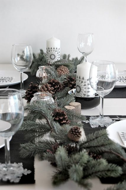 Bel centrotavola natalizio con pigne e candele.