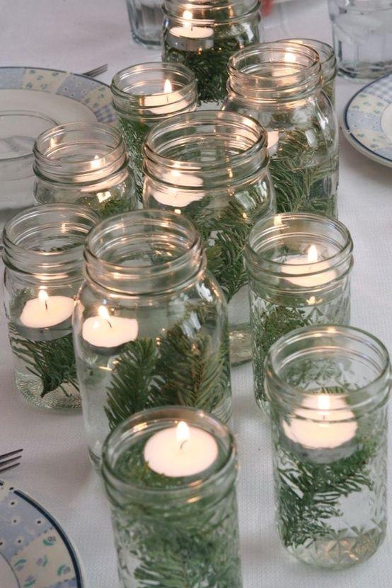Tavola di natale addobbata con barattoli di vetro e candele.