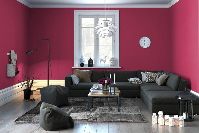Soggiorno con parete bordeaux e divano angolare grigio antracite.