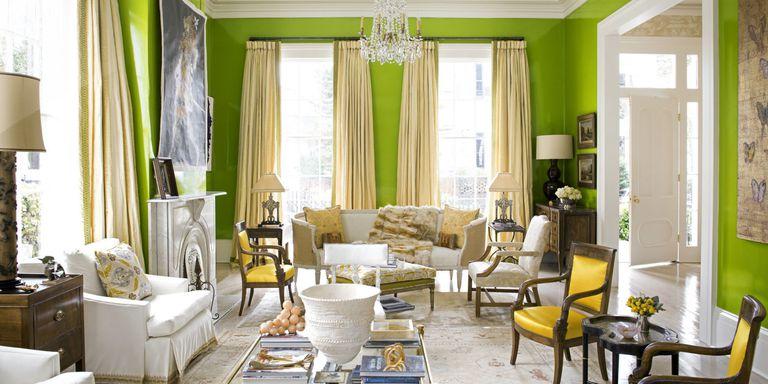 Salotto bellissimo con pareti verdi, tende beige e arredi bianchi.