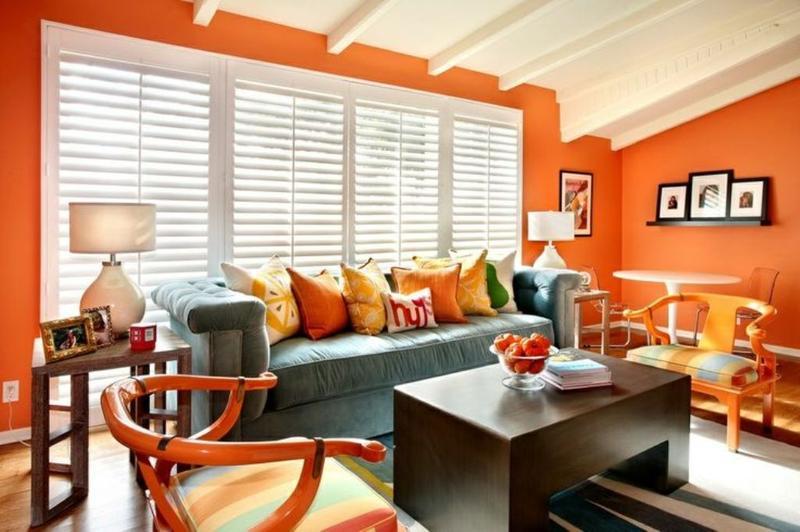 soggiorno moderno con pareti arancione e soffitto bianco con travi.