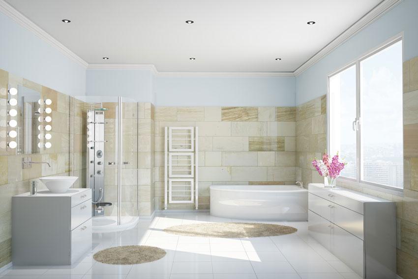 bagno contemporaneo con sanitari e mobili bianchi, rivestimento pareti color beige e crema.