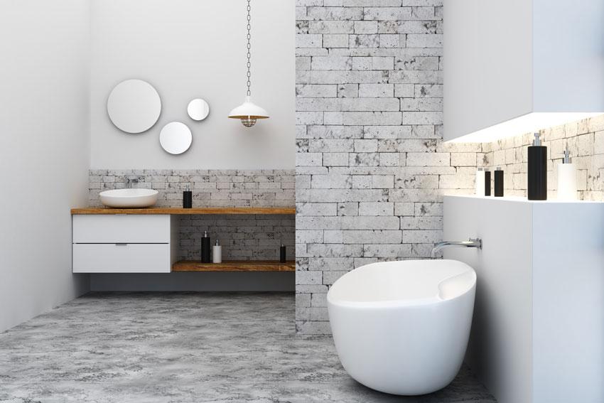 bagno moderno con rivestimento effetto pietra, vasca design.