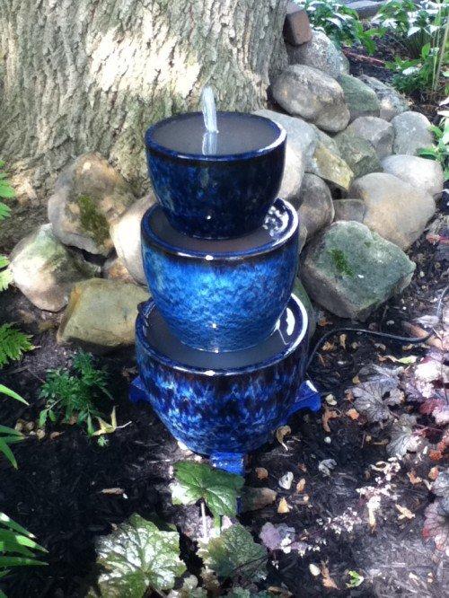 fontanella da giardino con vasetti colorati e pietre.