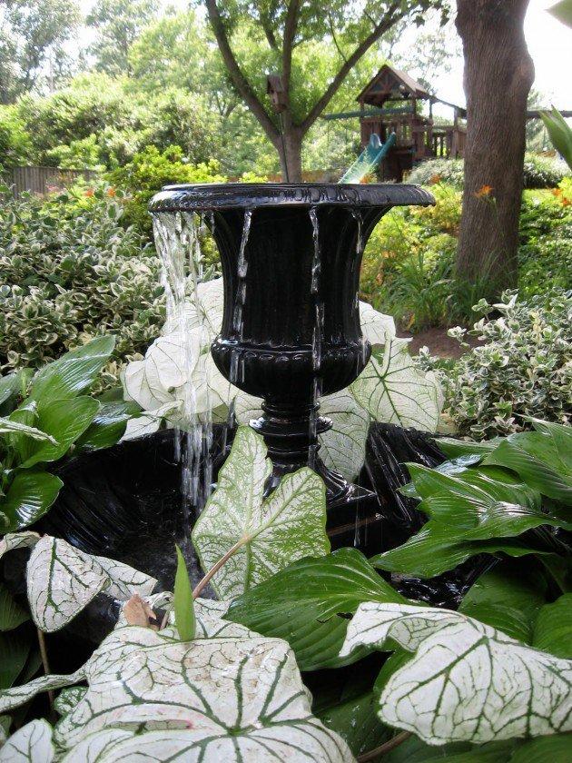 bella fontanella da giardino realizzata con un vaso nero centrale.
