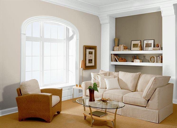 bellissimo soggiorno con divano beige e pareti tortora con pilastri bianchi