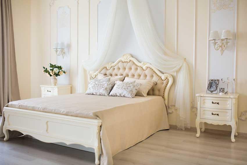 camera da letto stile shabby con tende a velo sopra al letto, bello il comodino bianco.