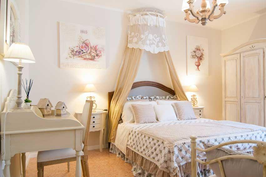 camera con arredamento shabby chic, letto con tende beige.