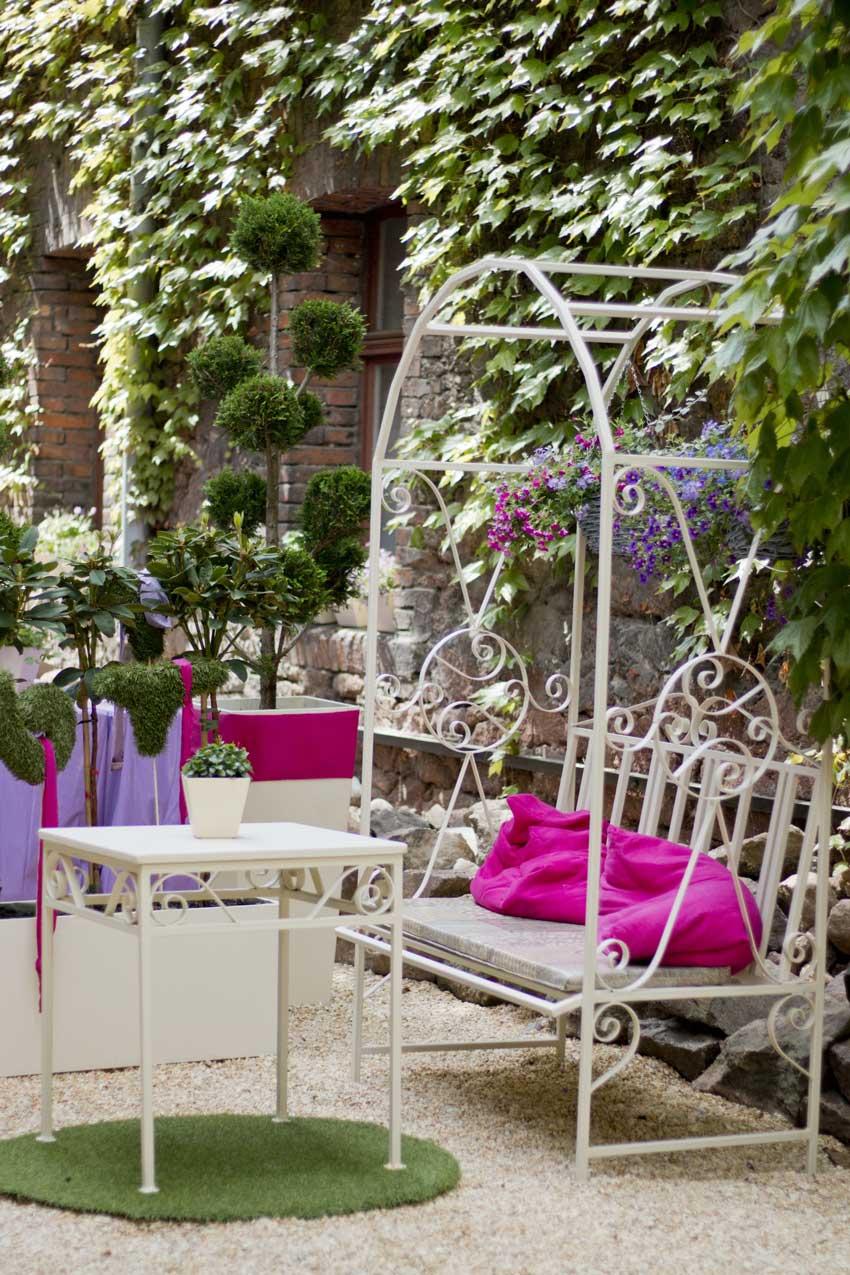 giardino arredato in stile shabby chic, tavolino in ferro battuto bianco.