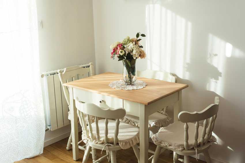 piccola sala da pranzo con arredamento shabby chic, tavolo con top in legno e vaso centrale.