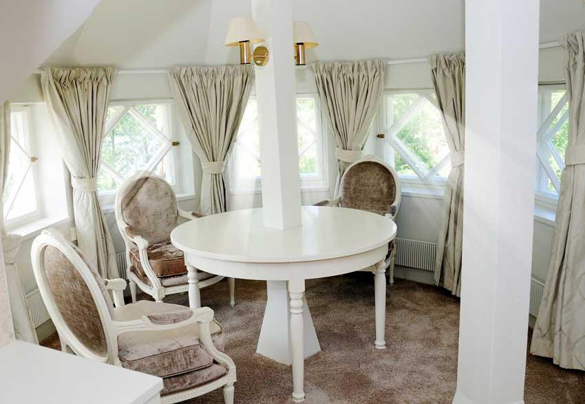 sala da pranzo con tavolo rotondo e sedie stile provenzale.