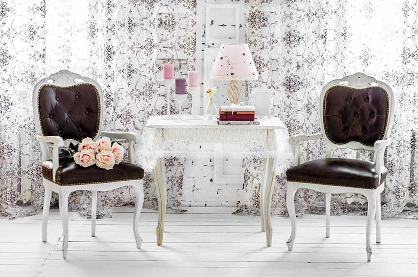 soggiorno con angolo shabby chic, tavolino bianco con tovaglia di pizzo e due sedie bianche con rivestimento marrone in pelle.
