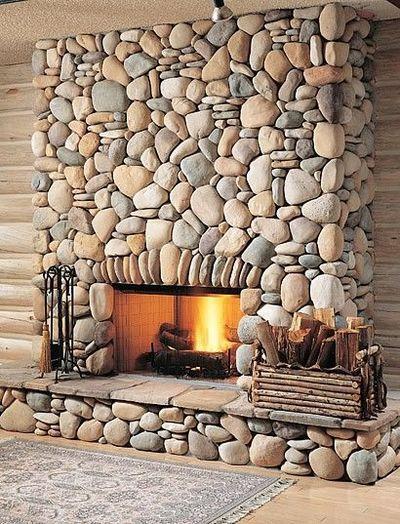 Caminetto rustico con rivestimento in pietra e sassi di colore grigio e beige.