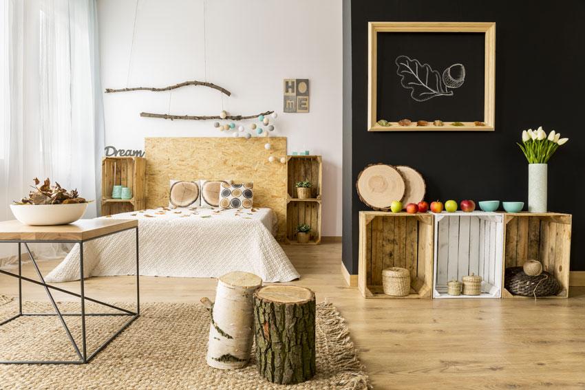camera da letto con arredamento fai da te, cassette di legno, tronchi di legno e testiera letto in legno.