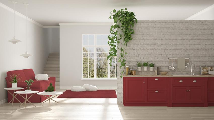 Cucina rossa lineare, pareti con mattoni bianchi a vista, ideale in una casa moderna.