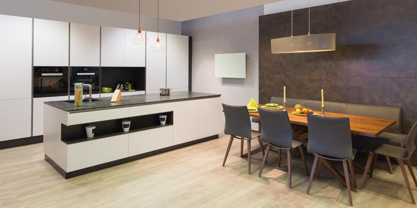 Cucina bianca lineare moderna con isola e rifiniture nere.