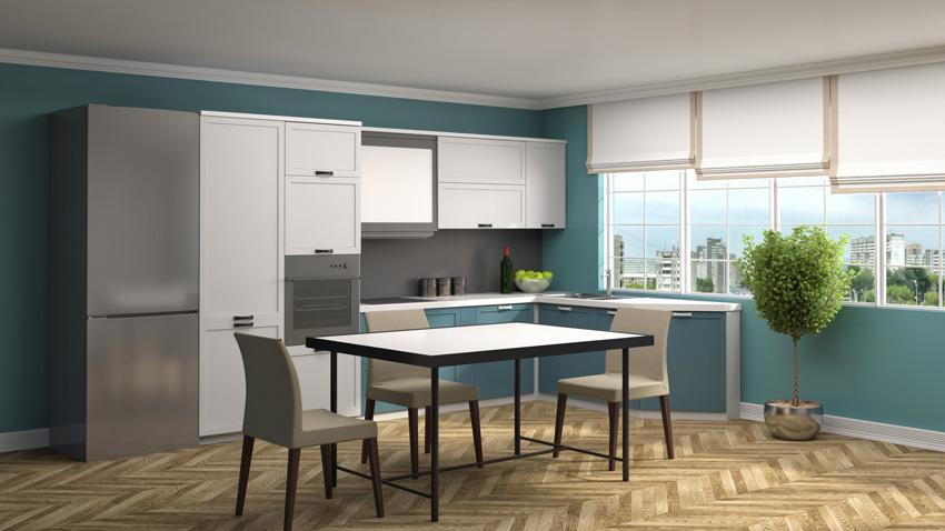 Cucina angolare con pareti blu e mobili bianchi.