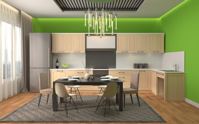 Cucina moderna con mobili legno chiaro e pareti verdi.