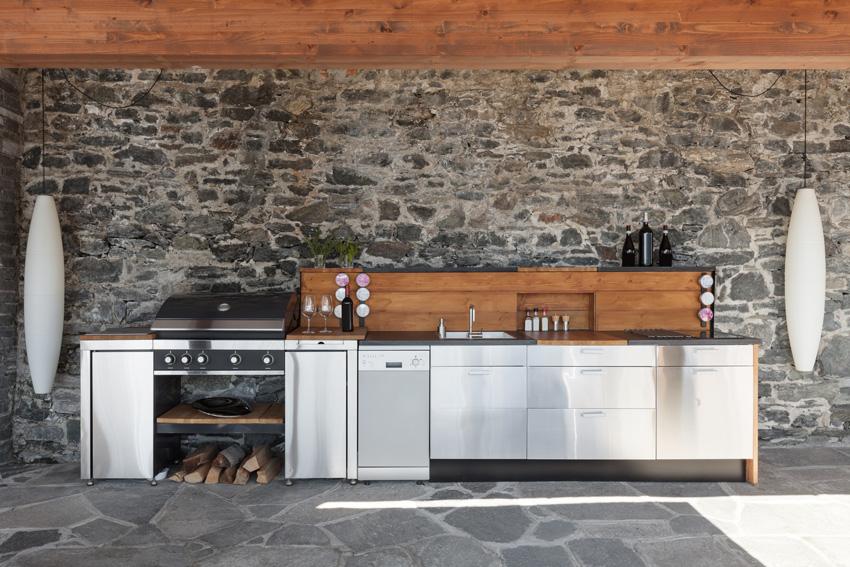 Cucina lineare con parete con pietre naturale a vista.