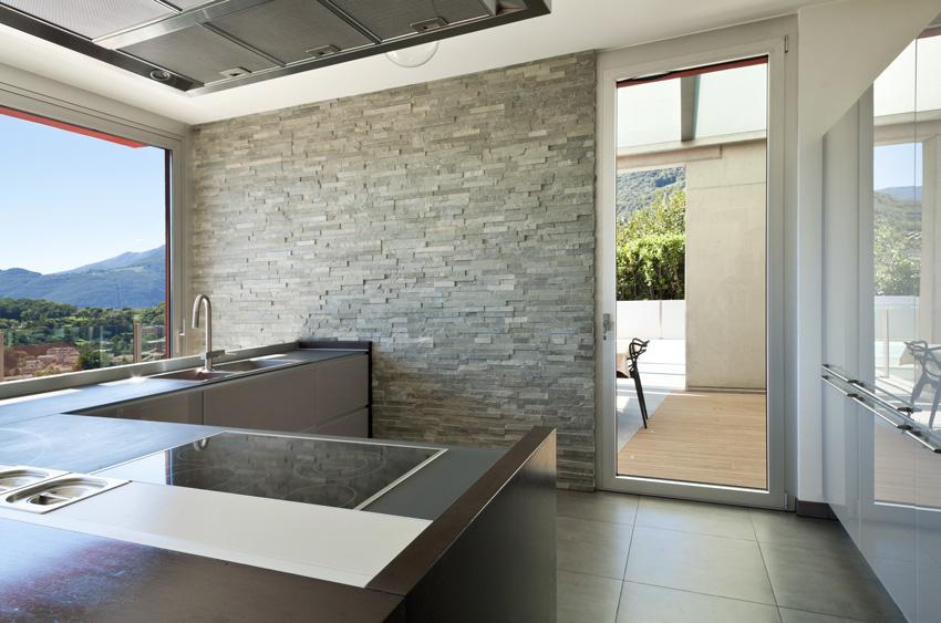 Cucina contemporanea con parete rivestita di pietra grigia.