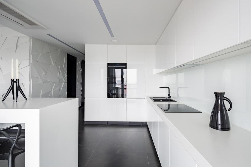 bella cucina bianca moderna con pavimenti neri ed elementi di arredi neri.