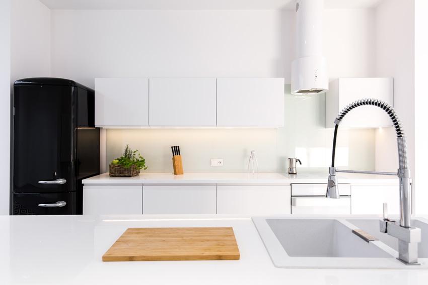 Cucina con isola bianca con frigorifero nero.