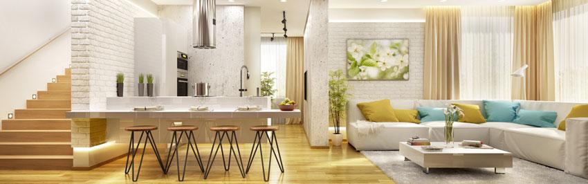 soggiorno e cucina open space moderno, luminoso, bianco con elementi colorati giallo e blu, pareti in mattoni bianchi.