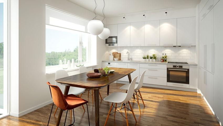 cucina moderna tutta bianca spezzata con pavimento in legno tipo parquet, bello anche il tavolo in legno.