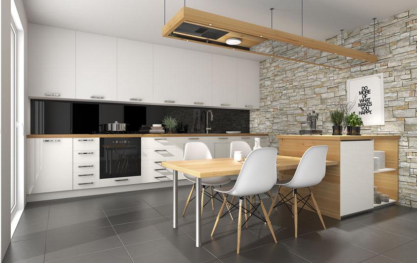 bella cucina design bianca con una parete rivestita in pietra, penisola in legno con sedie bianche e cappa sospesa.