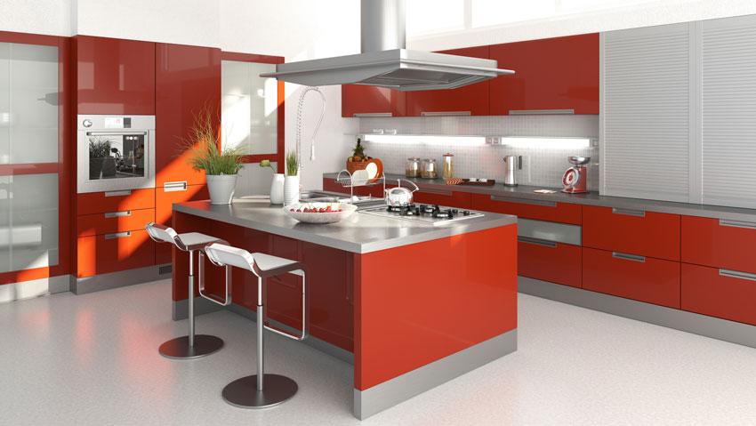 grande cucina rossa dal mood moderno, top e cappa sospesa in allumino grigio, grande isola.