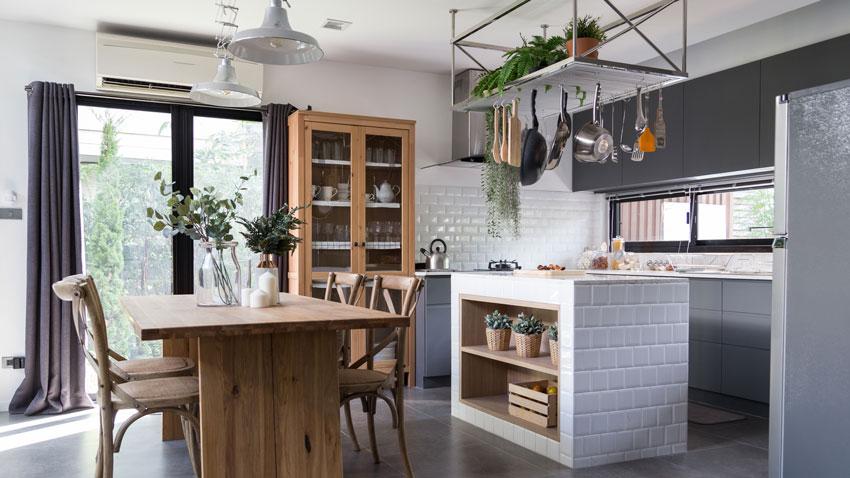 Bella cucina moderna con isola cucina in muratura rivestita di mattonelle tipo mattoni bianchi.