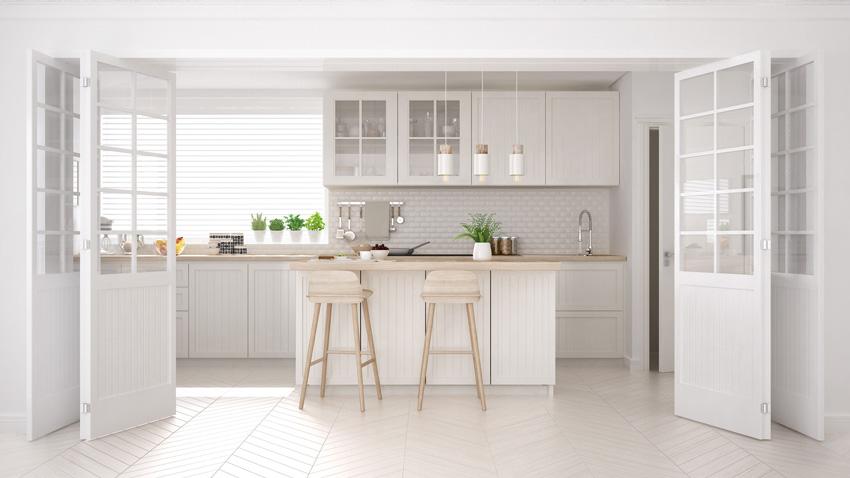 splendida cucina bianca dal design unico, top e sedie in legno chiaro, grande porte scorrevole.