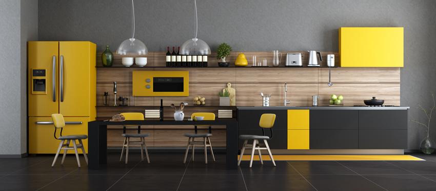 una cucina lineare moderna gialla e nera con paraschizzi effetto legno, grande frigorifero di colore giallo, pavimenti neri.