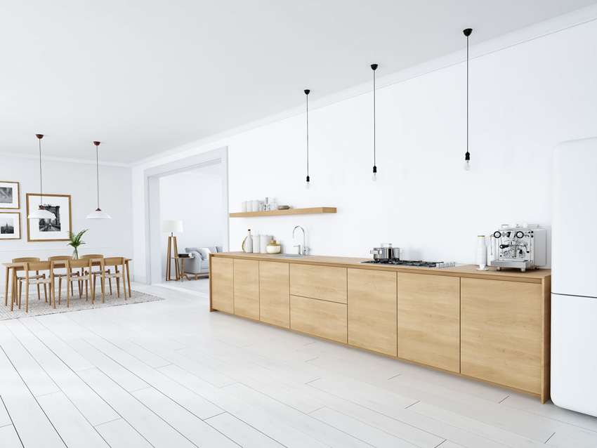 cucina in legno minimal con lampadine sospese, pareti di colore bianco, frigorifero bianco.
