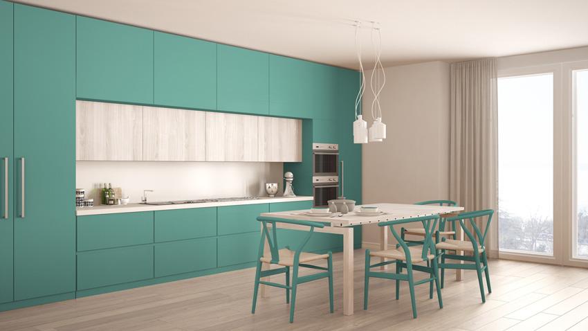 cucina di colore turchese con un tocco di grigio chiaro, tavolo in legno con sedie design abbinati ai mobili turchesi.