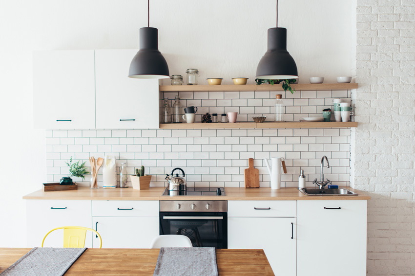 una cucina dallo stile contemporaneo, piccola lineare ma completa, mensole e top in legno.