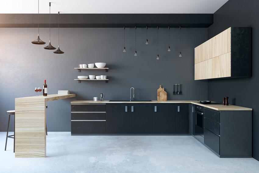 cucina moderna nera con pensili, top e penisola in legno, belle le lampadine sospese.