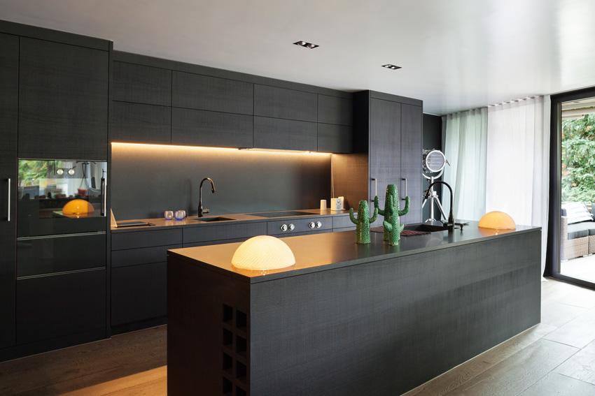 Cucina nera moderna con isola centrale e illuminazione design.