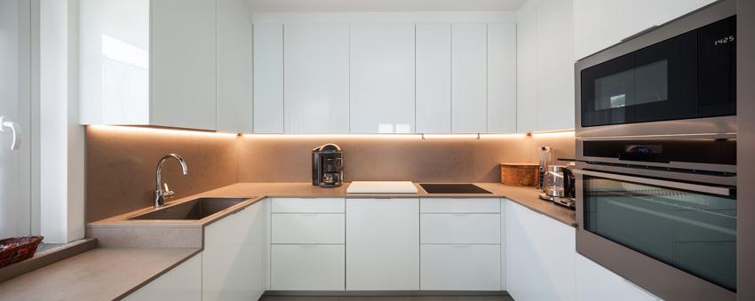 Cucina bianca lucida a forma di U, illuminazioni a luci LED sotto pensili.