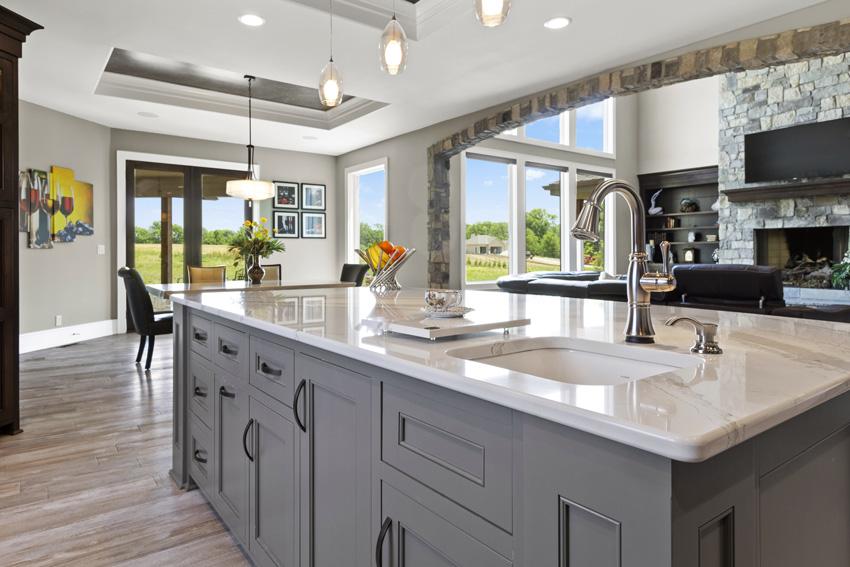 cucina con rivestimenti in pietra e isola con top in marmo, mobili grigi.