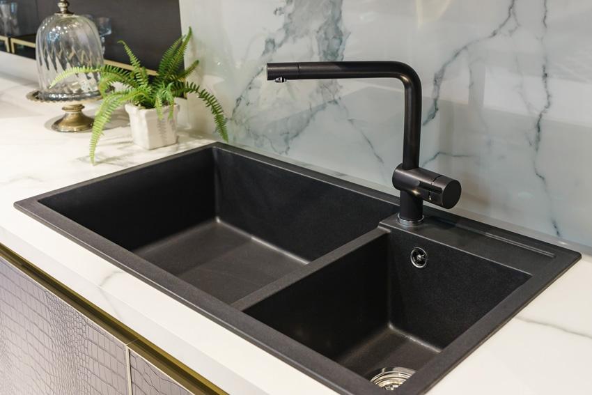 cucina con con lavandino e rubinetteria nero, paraschizzi in marmo.