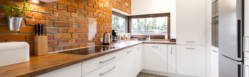 cucina moderna bianca con pareti in mattoni rossi, paraschizzi trasparente e top in legno.