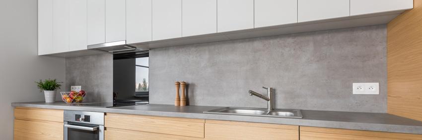 cucina contemporanea con paraschizzi grigi mobili in legno e pensili grigi chiaro.