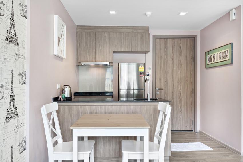 piccola cucina in stile moderno arredata alla perfezione con rivestimenti abbinati alla porta.