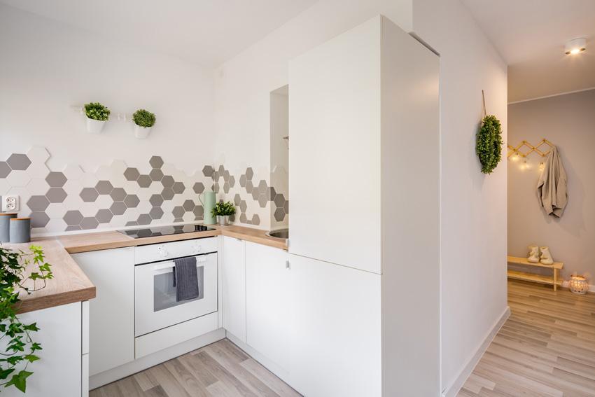 cucina ad angolo stile moderno con top il legno chiaro e mattonelle originali grigie e bianche.