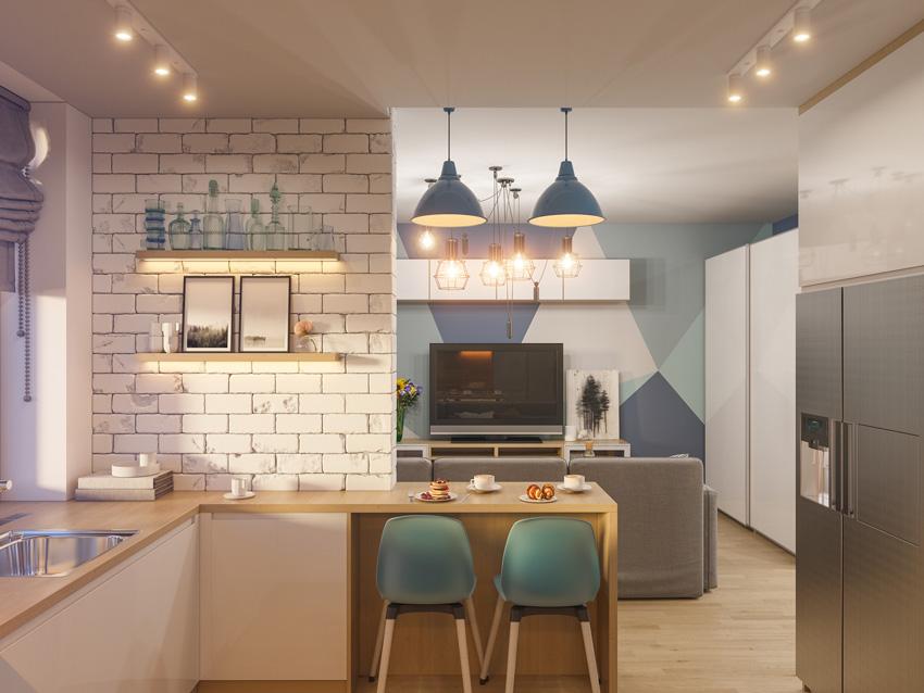 Cucina angolare con piccola penisola in legno e parete con mattoni a vista bianchi.