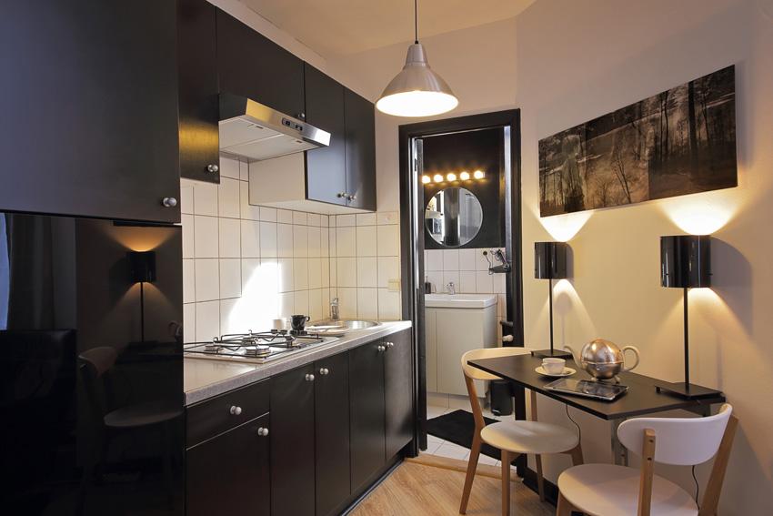 piccola cucina bianco e nero stile moderno, tavolino nero con sedie bianche.