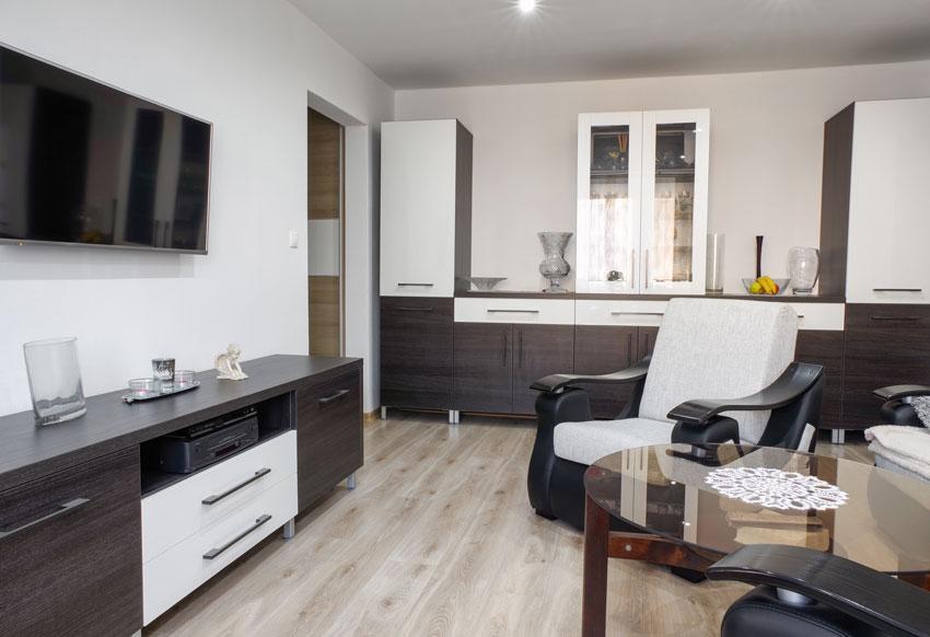 piccolo salotto moderno arredato con mobili bianchi e marroni, tavolino in vetro e poltrone design.